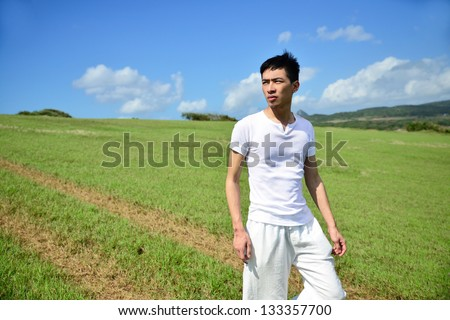 young man running down bright green grass on summer