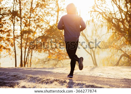 Young man running during autumn, winter morning. Healthy lifestyle concept - stock photo
