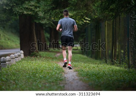 Young Man Running In Wooded Forest Area - Training And Exercising For Trail Run Marathon Endurance - Fitness Healthy Lifestyle Concept - stock photo
