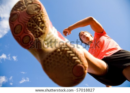young man running lifting his feet high against the blue sky. Bottom view - stock photo