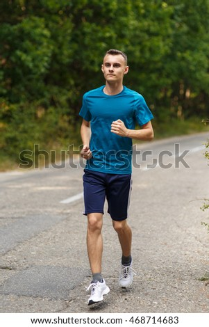 Young man running on a road through the forest