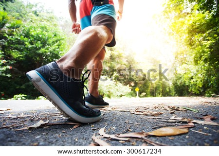 Young man running on a rural road during sunset at streets dry leaf