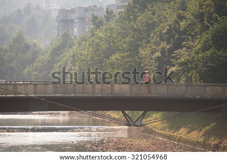 Young Man Running On Bridge In Wooded Forest Area - Training And Exercising For Trail Run Marathon Endurance - Fitness Healthy Lifestyle Concept - stock photo