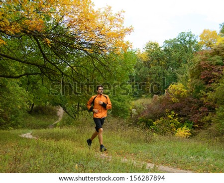 Young Man Running on the Trail in the Beautiful Autumn Forest - stock photo