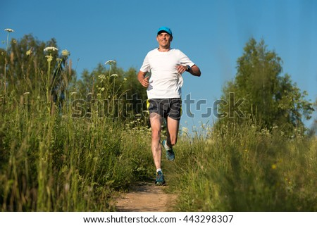 Young man running on trail In forest