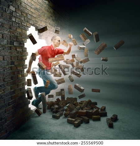 Young man running through a brick wall - stock photo