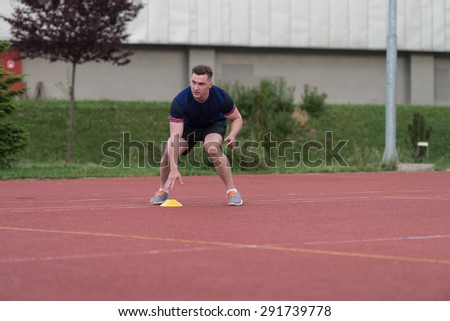 Young Man Running To The Cone On Sports Field