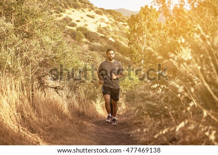 Young man running up a gravel path in the late afternoon sunshine with trees behind, while wearing casual clothing