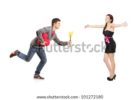Young man running with a bunch of flowers and red heart shape object and excited female isolated on white background - stock photo