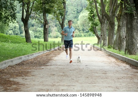 Young man running with your dog - stock photo