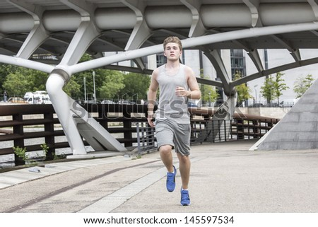 Young man runs at the town center waters  - stock photo