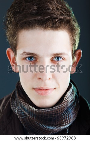 Young man's face on dark  background - stock photo