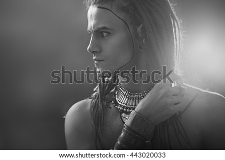 Young man's portrait. Stylish handsome sexy Guy with Dreadlocks and ethnic Jewelry, Accessories (necklace, bracelet) Close-up face. Tribal Style. Trendy youthful man's look, war paint