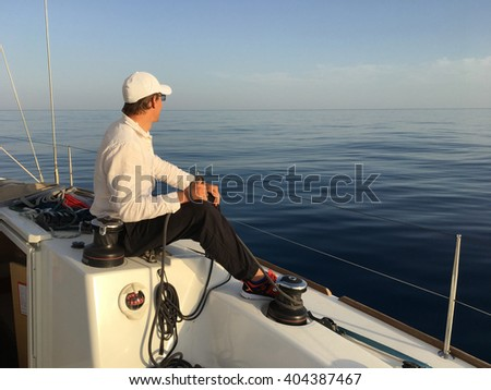 Young man sailing yacht yachtsman holding hands rope vacation sail holidays people travel