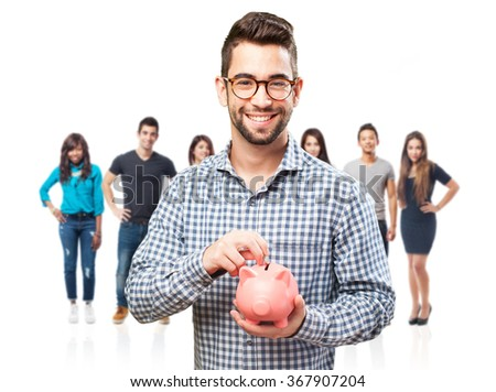 young man saving with piggy bank - stock photo