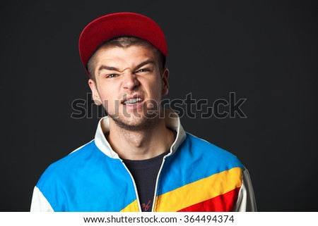 Young man saw something disgusting - isolated on dark background. - stock photo