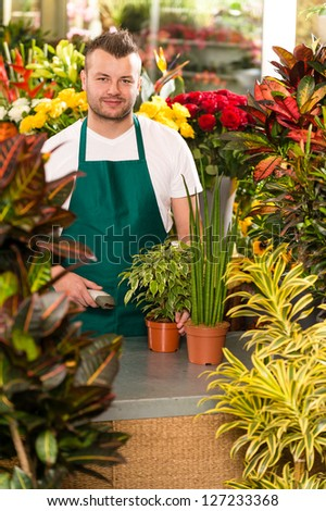 Young man scanning bar-code flower shop gardening florist - stock photo