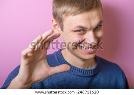 Young man scared smiling, joking. Gesture. On a purple background. - stock photo