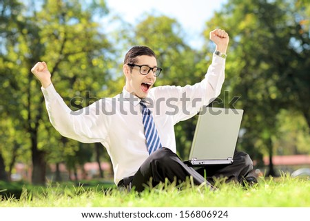 Young man screaming and watching TV on a laptop in a park outside - stock photo