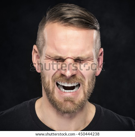 Young man screaming on a dark background.  - stock photo