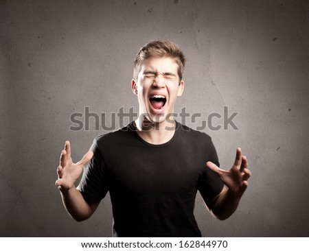 young man screaming on a grey background - stock photo
