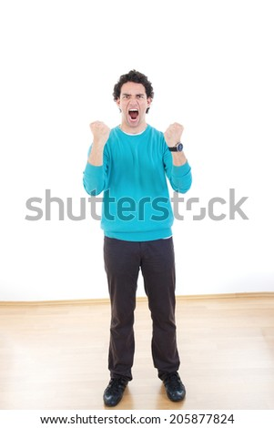 Young man screaming standing with clenched fists with expression - stock photo