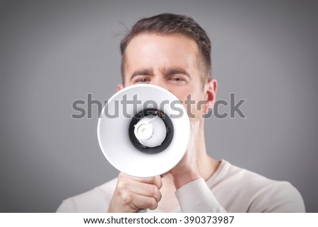 Young man screaming with a megaphone on grey background