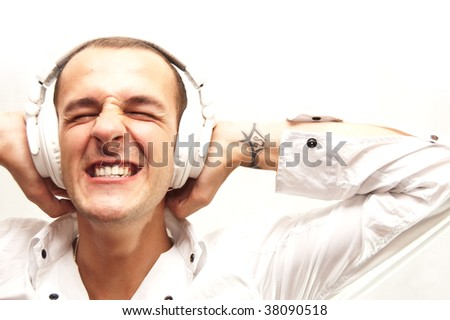 young man screams almost because of the loud music in his headphones - stock photo