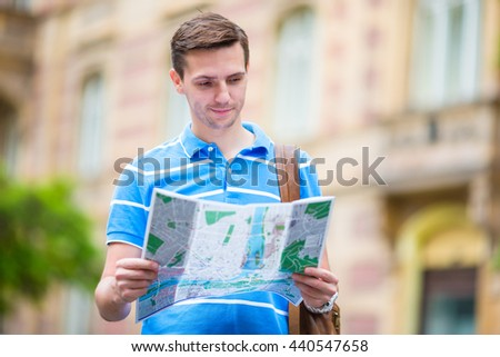 Young man searching the street with a city map in Europe. Caucasian tourist looking at the map of European city in search of attractions. - stock photo