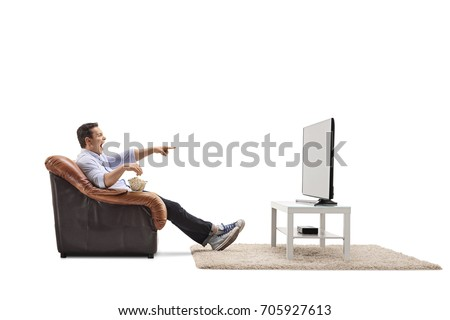 Young man seated in an armchair watching television and laughing isolated on white background
