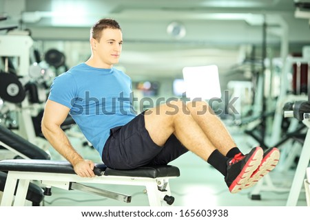 Young man seated on a bench exercising abdominal muscles in a fitness club - stock photo