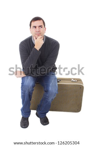 young man seated on a suitcase, isolated on white background - stock photo
