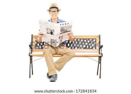 Young man seated on a wooden bench holding newspaper and looking at camera isolated on white background - stock photo