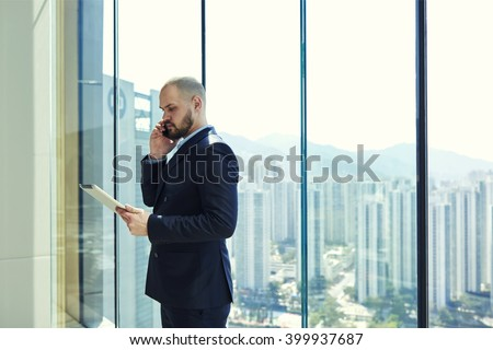 Young man serious managing director is calling to his manager to find out why he had not sent to email on digital tablet reporting on implementation of work, while is standing near office window