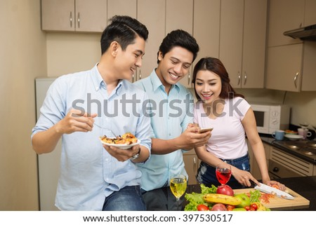 Young man sharing funny photo on his phone with friends