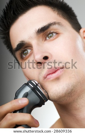 young man shaving his beard off with an electric razor - stock photo