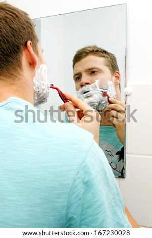 young man shaving his face, reflection in mirror - stock photo