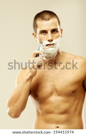 young man shaving in the bath. He is passing the razor for the beard while it looks at the mirror - stock photo