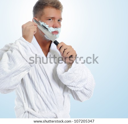 Young man shaving in the morning close-up.