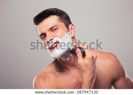 Young man shaving with foam and razor over gray background - stock photo