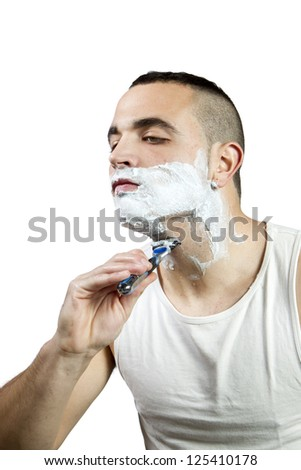 Young man shaving with razor and foam