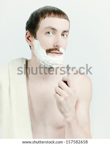 young man shaving with towel on the shoulders.