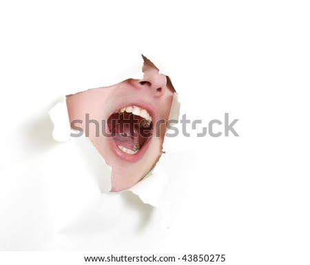 young man shouting loudly through hole in paper - stock photo