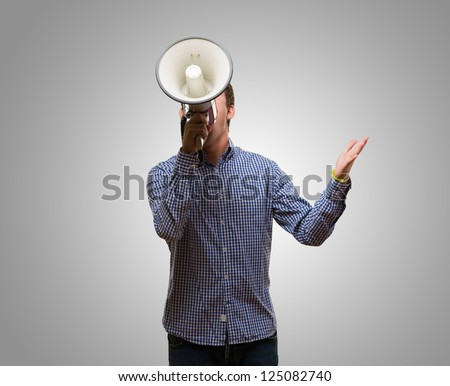 Young Man Shouting On Megaphone against a grey background