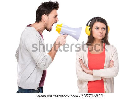 Young man shouts at the woman in a megaphone. Woman with headphones while he screams. White background. - stock photo