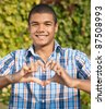 Young man show love sign outdoor - stock photo