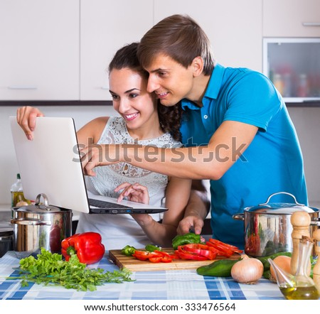 Young man showing cooking housewife something on laptop screen