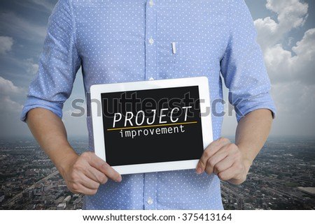 young man showing digital tablet with PROJECT IMPROVEMENT  on sky blackground  , business concept ,business idea - stock photo