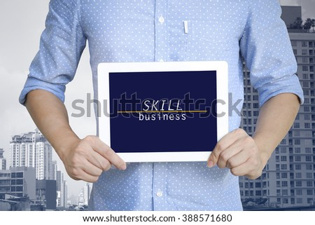 young man showing digital tablet with SKILL BUSINESS  in city , business concept ,business idea , strategy concept - stock photo
