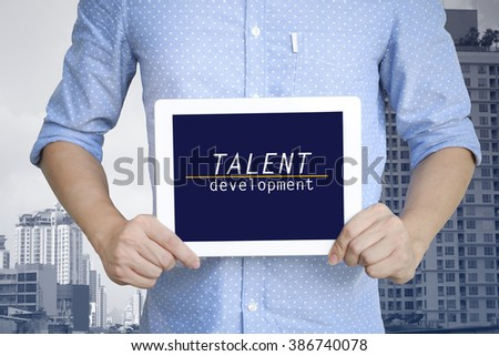 young man showing digital tablet with TALENT DEVELOPMENT in city  , business concept ,business idea , strategy concept - stock photo